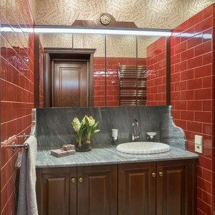 Создайте стильный интерьер: ванная комната среднего размера в викторианском стиле с фасадами с выступающей филенкой, темными деревянными фасадами, красной плиткой, накладной раковиной и серым полом - последний тренд