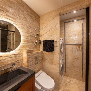 Стильный дизайн: ванная комната среднего размера в современном стиле с плоскими фасадами, черными фасадами, душем в нише, инсталляцией, бежевой плиткой, керамогранитной плиткой, бежевыми стенами, полом из керамогранита, душевой кабиной, монолитной раковиной, бежевым полом, душем с распашными дверями, черной столешницей, тумбой под одну раковину и встроенной тумбой - последний тренд