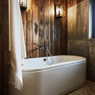 Mid-sized country master bathroom in Other with a freestanding tub, brown walls, grey floor, wood and wood walls.