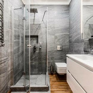Свежая идея для дизайна: ванная комната в современном стиле с плоскими фасадами, белыми фасадами, угловым душем, серой плиткой, паркетным полом среднего тона, монолитной раковиной, коричневым полом, душем с распашными дверями и подвесной тумбой - отличное фото интерьера