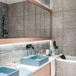 На фото: главные ванные комнаты в современном стиле с плоскими фасадами, светлыми деревянными фасадами, серой плиткой, настольной раковиной, серым полом, белой столешницей и ванной в нише
