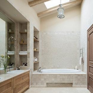 Свежая идея для дизайна: главная ванная комната в стиле современная классика с фасадами с утопленной филенкой, фасадами цвета дерева среднего тона, накладной ванной, бежевой плиткой, плиткой из травертина, бежевыми стенами, полом из травертина, накладной раковиной и бежевым полом - отличное фото интерьера