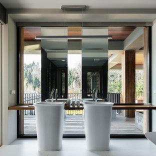 На фото: главные ванные комнаты в современном стиле с белыми стенами, консольной раковиной, белым полом и коричневой столешницей