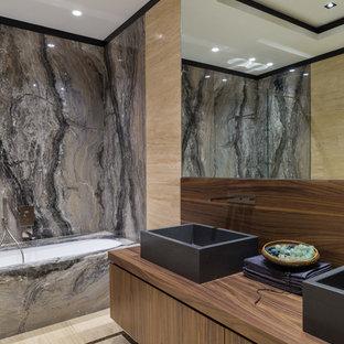 Новый формат декора квартиры: большая главная ванная комната в современном стиле с плоскими фасадами, полновстраиваемой ванной, плиткой из листового камня, полом из травертина, столешницей из дерева, настольной раковиной, темными деревянными фасадами, душем над ванной, черной плиткой, серой плиткой и бежевыми стенами