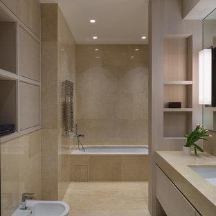 Удачное сочетание для дизайна помещения: большая ванная комната в современном стиле с плоскими фасадами, светлыми деревянными фасадами, полновстраиваемой ванной, бежевой плиткой, плиткой из листового камня, бежевыми стенами, полом из травертина, врезной раковиной, мраморной столешницей, душем над ванной, биде и бежевым полом - самое интересное для вас