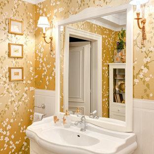 Источник вдохновения для домашнего уюта: ванная комната в стиле неоклассика (современная классика) с белыми фасадами, желтыми стенами, монолитной раковиной, тумбой под одну раковину и обоями на стенах