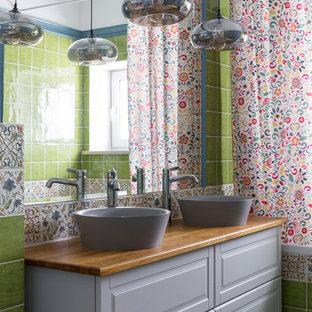 Неиссякаемый источник вдохновения для домашнего уюта: ванная комната в стиле современная классика с фасадами с выступающей филенкой, серыми фасадами, ванной в нише, душем над ванной, зеленой плиткой, разноцветной плиткой, белыми стенами, настольной раковиной, столешницей из дерева, серым полом, шторкой для душа и коричневой столешницей