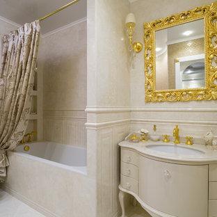 Пример оригинального дизайна: главная ванная комната среднего размера в классическом стиле с бежевыми фасадами, ванной в нише, душем над ванной, бежевой плиткой, керамической плиткой, полом из керамической плитки, врезной раковиной, мраморной столешницей, бежевым полом, шторкой для душа, плоскими фасадами, биде и бежевой столешницей