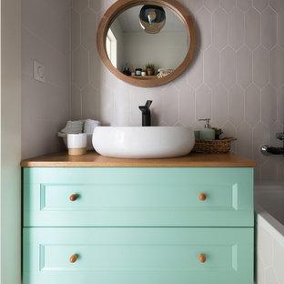Diseño de cuarto de baño contemporáneo con armarios con paneles empotrados, puertas de armario verdes, bañera empotrada, baldosas y/o azulejos marrones, lavabo sobreencimera, encimera de madera, suelo multicolor y encimeras marrones