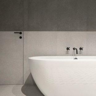 На фото: главная ванная комната в современном стиле с отдельно стоящей ванной, серой плиткой, керамогранитной плиткой, полом из керамогранита и серым полом с