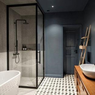 Exemple d'une grande salle de bain principale tendance avec une baignoire indépendante, un carrelage gris, des carreaux de porcelaine, un sol en carreaux de ciment, une vasque, un sol multicolore, une cabine de douche à porte battante, un mur bleu, un placard à porte plane, des portes de placard en bois brun et une douche d'angle.