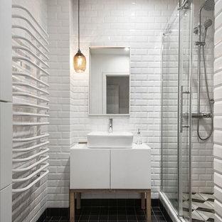 Удачное сочетание для дизайна помещения: маленькая ванная комната в скандинавском стиле с плоскими фасадами, белыми фасадами, душем в нише, белой плиткой, черно-белой плиткой, черной плиткой, белыми стенами, полом из керамической плитки, душевой кабиной, плиткой кабанчик, настольной раковиной, черным полом и душем с раздвижными дверями - самое интересное для вас