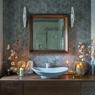 Пример оригинального дизайна интерьера: ванная комната в современном стиле с плоскими фасадами, темными деревянными фасадами, серой плиткой, душевой кабиной, настольной раковиной, столешницей из дерева, коричневой столешницей, серыми стенами и душем с распашными дверями