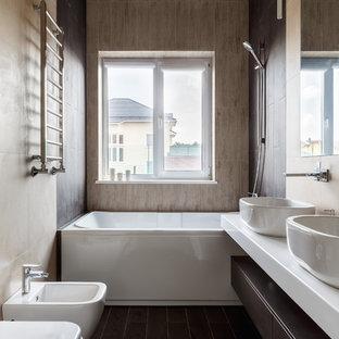 На фото: маленькая главная ванная комната в современном стиле с плоскими фасадами, темными деревянными фасадами, ванной в нише, биде, бежевой плиткой, керамогранитной плиткой, полом из керамогранита, столешницей из искусственного кварца, коричневым полом, белой столешницей и настольной раковиной