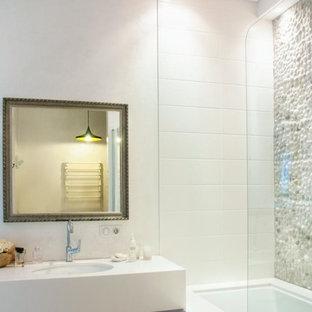 Ispirazione per una stanza da bagno padronale contemporanea di medie dimensioni con vasca sottopiano, WC sospeso, piastrelle bianche, piastrelle di ciottoli, pareti bianche, pavimento con piastrelle in ceramica, lavabo sottopiano e top in quarzo composito