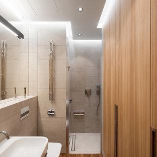 Стильный дизайн: маленькая ванная комната в современном стиле с серой плиткой, паркетным полом среднего тона, душевой кабиной и коричневым полом - последний тренд
