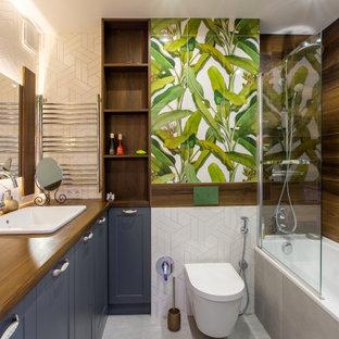 На фото: ванная комната среднего размера в стиле современная классика с фасадами в стиле шейкер, синими фасадами, ванной в нише, душем над ванной, инсталляцией, белой плиткой, керамогранитной плиткой, полом из керамогранита, душевой кабиной, накладной раковиной, столешницей из дерева, серым полом, коричневой столешницей, тумбой под одну раковину и встроенной тумбой с