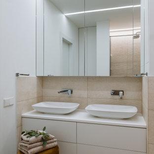 На фото: ванная комната в современном стиле с плоскими фасадами, белыми фасадами, бежевой плиткой, белыми стенами, настольной раковиной, коричневым полом и белой столешницей с