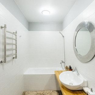Foto di una piccola stanza da bagno scandinava con vasca ad alcova, vasca/doccia, piastrelle bianche, piastrelle in ceramica, pareti grigie, pavimento in gres porcellanato, lavabo da incasso, top in legno e pavimento grigio