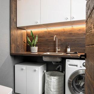 Свежая идея для дизайна: маленькая ванная комната со стиральной машиной в скандинавском стиле с плоскими фасадами, белыми фасадами, серыми стенами, полом из керамогранита, серым полом, накладной раковиной, столешницей из дерева, коричневой столешницей и тумбой под одну раковину - отличное фото интерьера