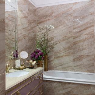 Inredning av ett klassiskt badrum, med lila skåp, ett undermonterat badkar, beige kakel, ett undermonterad handfat och flerfärgat golv