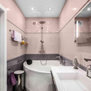 Idee per una stanza da bagno design con vasca ad angolo, vasca/doccia, piastrelle rosa, piastrelle grigie, lavabo integrato e pavimento grigio