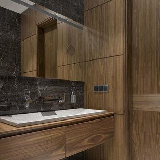 На фото: ванные комнаты среднего размера в современном стиле с плоскими фасадами, фасадами цвета дерева среднего тона, серой плиткой, керамогранитной плиткой, мраморным полом, столешницей из дерева, раковиной с несколькими смесителями и коричневой столешницей
