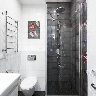 На фото: ванная комната в современном стиле с угловым душем, инсталляцией, керамической плиткой, полом из керамической плитки, душевой кабиной, плоскими фасадами, белыми фасадами, белой плиткой, черной плиткой, черным полом и белыми стенами с