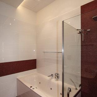 Esempio di una stanza da bagno padronale contemporanea di medie dimensioni con vasca da incasso, piastrelle rosse, piastrelle in gres porcellanato, pareti rosa, pavimento in gres porcellanato, lavabo sospeso, vasca/doccia, pavimento rosso e porta doccia a battente