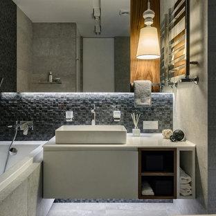 Идея дизайна: главная ванная комната в современном стиле с плоскими фасадами, белыми фасадами, ванной в нише, серой плиткой, настольной раковиной, серым полом, инсталляцией, плиткой мозаикой, серыми стенами, бетонным полом и открытым душем