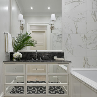 На фото: главная ванная комната среднего размера в стиле современная классика с белыми фасадами, серой плиткой, мраморной столешницей, стеклянными фасадами, полновстраиваемой ванной, белыми стенами, врезной раковиной и черным полом с