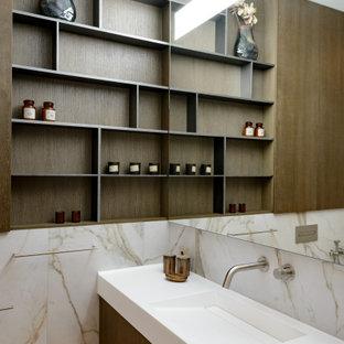 Стильный дизайн: ванная комната в современном стиле с темными деревянными фасадами, монолитной раковиной, плоскими фасадами, разноцветной плиткой, плиткой из листового камня и белой столешницей - последний тренд