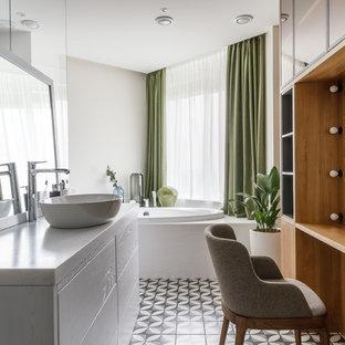 Стильный дизайн: большая главная ванная комната в современном стиле с коричневыми фасадами, ванной в нише, керамической плиткой, белыми стенами, полом из керамической плитки, настольной раковиной и фасадами островного типа - последний тренд