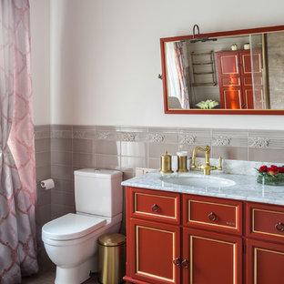 Esempio di una stanza da bagno classica di medie dimensioni con ante rosse, piastrelle beige, piastrelle in gres porcellanato, pareti bianche, pavimento in gres porcellanato, lavabo sottopiano, top in marmo, WC a due pezzi e consolle stile comò