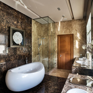 Inspiration for a contemporary ensuite bathroom in Moscow with a corner shower, brown walls, a built-in sink, a freestanding bath, brown tiles, stone slabs, marble flooring and a hinged door.