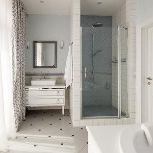 На фото: главные ванные комнаты в стиле современная классика с белыми фасадами, накладной ванной, душем в нише, белой плиткой, синими стенами, настольной раковиной, белым полом и душем с распашными дверями