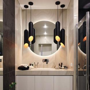 Неиссякаемый источник вдохновения для домашнего уюта: ванная комната среднего размера в современном стиле с плоскими фасадами, белыми фасадами, керамогранитной плиткой, полом из керамогранита, душевой кабиной, столешницей из плитки, душем с распашными дверями, бежевой плиткой, накладной раковиной, бежевым полом, бежевой столешницей и душем в нише