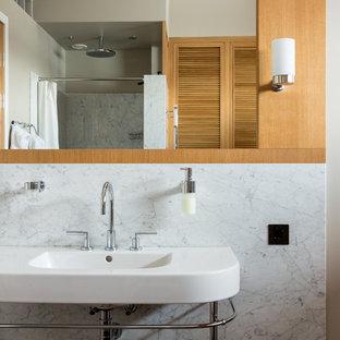 Идея дизайна: главная ванная комната в современном стиле с фасадами с филенкой типа жалюзи, фасадами цвета дерева среднего тона, серой плиткой, белой плиткой, мраморной плиткой, бежевыми стенами, консольной раковиной и белой столешницей