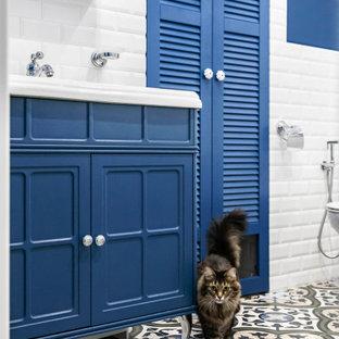Diseño de cuarto de baño principal, tradicional renovado, de tamaño medio, con armarios con puertas mallorquinas, puertas de armario azules, bañera esquinera, combinación de ducha y bañera, sanitario de pared, baldosas y/o azulejos blancos, baldosas y/o azulejos de cerámica, paredes azules, suelo de baldosas de porcelana, suelo multicolor y ducha con cortina