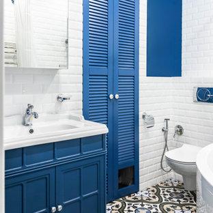 Идея дизайна: главная ванная комната среднего размера в стиле современная классика с фасадами с филенкой типа жалюзи, синими фасадами, угловой ванной, душем над ванной, инсталляцией, белой плиткой, керамической плиткой, синими стенами, полом из керамогранита, разноцветным полом и шторкой для душа
