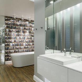 Создайте стильный интерьер: главная ванная комната среднего размера в современном стиле с отдельно стоящей ванной, плоскими фасадами, белыми фасадами, разноцветной плиткой, серыми стенами, полом из линолеума и накладной раковиной - последний тренд