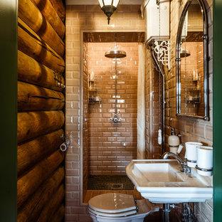 Imagen de cuarto de baño con ducha, rústico, con ducha empotrada, sanitario de dos piezas, baldosas y/o azulejos beige, baldosas y/o azulejos de cemento, paredes marrones, lavabo suspendido y ducha con cortina