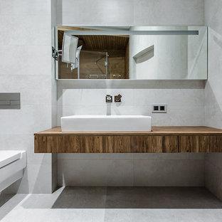 Новый формат декора квартиры: ванная комната в современном стиле с инсталляцией, серой плиткой, настольной раковиной и серым полом