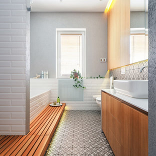 Inspiration for a contemporary bathroom in Other with flat-panel cabinets, medium wood cabinets, a drop-in tub, a bidet, multi-coloured tile, grey walls, a vessel sink, multi-coloured floor and white benchtops.