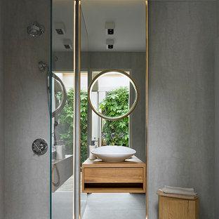 На фото: ванная комната в современном стиле с плоскими фасадами, фасадами цвета дерева среднего тона, отдельно стоящей ванной, серыми стенами, душевой кабиной, настольной раковиной и серым полом с