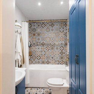 Photo of a small mediterranean shower room in Saint Petersburg with an alcove bath, a shower/bath combination, grey tiles, porcelain tiles, white walls, multi-coloured floors, a shower curtain, white worktops, raised-panel cabinets, blue cabinets, a two-piece toilet, cement flooring and an integrated sink.