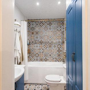На фото: маленькая ванная комната в средиземноморском стиле с ванной в нише, душем над ванной, серой плиткой, керамогранитной плиткой, белыми стенами, разноцветным полом, шторкой для ванной, белой столешницей, фасадами с выступающей филенкой, синими фасадами, раздельным унитазом, полом из цементной плитки, душевой кабиной и монолитной раковиной с