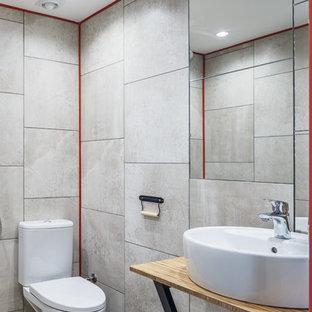 На фото: маленькая ванная комната в современном стиле с бежевой плиткой, керамогранитной плиткой, настольной раковиной, столешницей из дерева, открытыми фасадами, раздельным унитазом и серым полом с