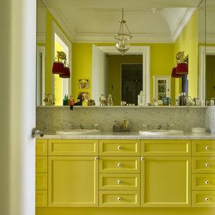 Esempio di una stanza da bagno padronale eclettica con ante con riquadro incassato, ante gialle, pareti gialle, pavimento con piastrelle in ceramica e lavabo da incasso