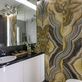 На фото: главная ванная комната среднего размера в современном стиле с плоскими фасадами, белыми фасадами, ванной в нише, душем над ванной, инсталляцией, разноцветной плиткой, керамогранитной плиткой, разноцветными стенами, полом из керамогранита, врезной раковиной, столешницей из искусственного камня, черным полом, шторкой для ванной, черной столешницей, нишей, тумбой под одну раковину, напольной тумбой и обоями на стенах с